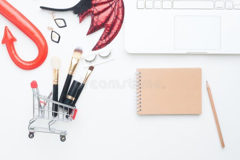 Στοιχεία ομορφιάς στο κάρρο αγορών με το κοστούμι, το φορητό προσωπικό υπολογιστή και το σημειωματάριο με το διάστημα αντιγράφων, στοκ φωτογραφίες