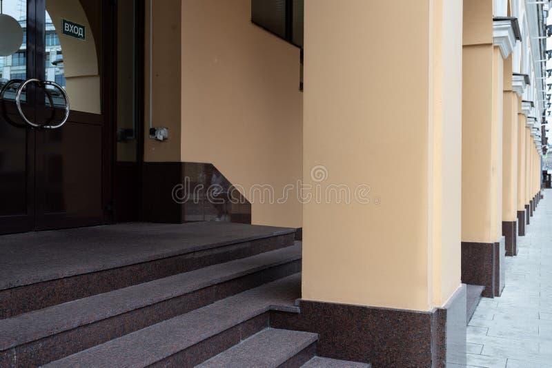 Στοιχεία της αστικής αρχιτεκτονικής, σκαλοπάτια που οδηγούν στην πόρτα, στήλες οικοδόμησης, επαναλαμβανόμενα στοιχεία στοκ εικόνες