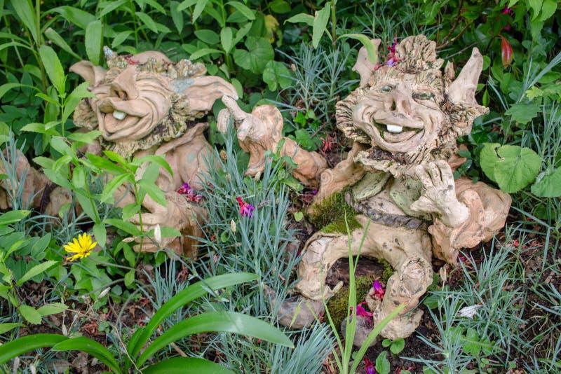 Στοιχειά κήπων με τα άτακτα χαμόγελα που κάθονται στα λουλούδια και τη χλόη ι στοκ εικόνες