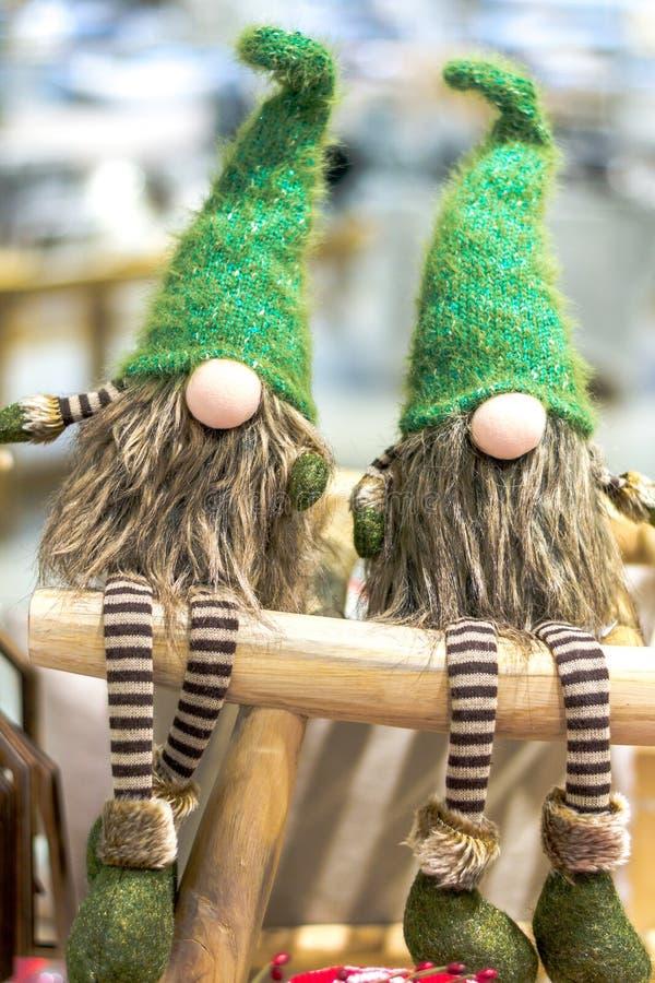 Στοιχειά Χριστουγέννων στα πράσινα καλύμματα και τα ριγωτά εσώρουχα Καθίστε σε ένα ξύλινο σκαμνί στοκ φωτογραφία με δικαίωμα ελεύθερης χρήσης