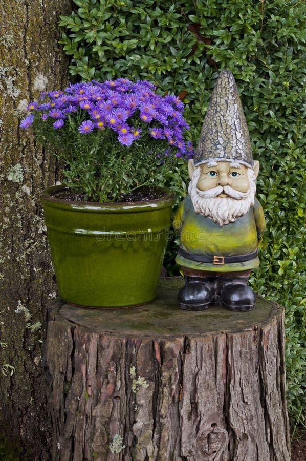 Στοιχειό που στέκεται στο κολόβωμα δέντρων δίπλα στα λουλούδια αστέρων στοκ φωτογραφία
