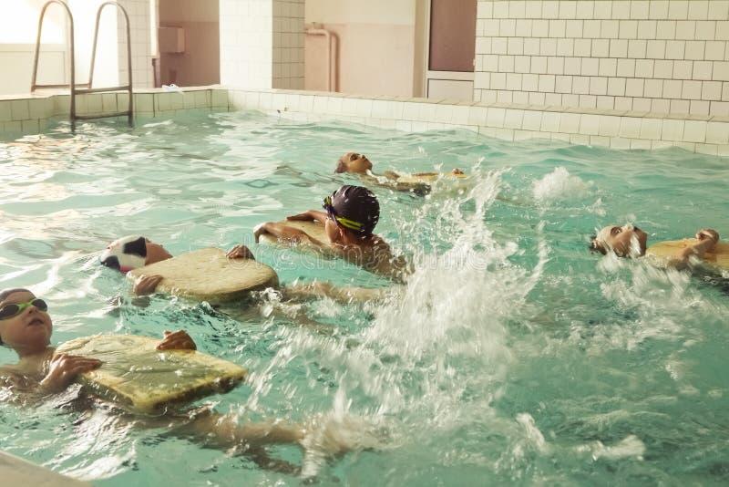 Στοιχειώδη παιδιά σχολείου μέσα στο μάθημα δεξιοτήτων κολύμβησης στοκ εικόνες