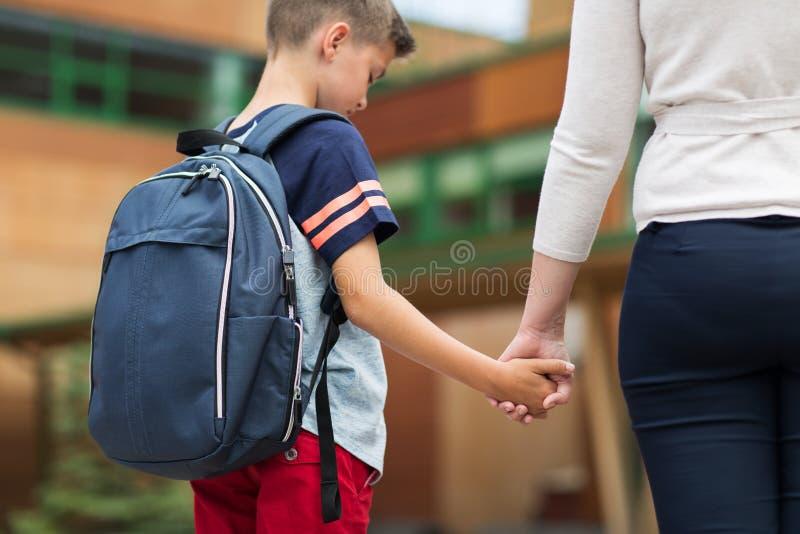 Στοιχειώδες αγόρι σπουδαστών με τη μητέρα στο σχολικό ναυπηγείο στοκ εικόνα με δικαίωμα ελεύθερης χρήσης
