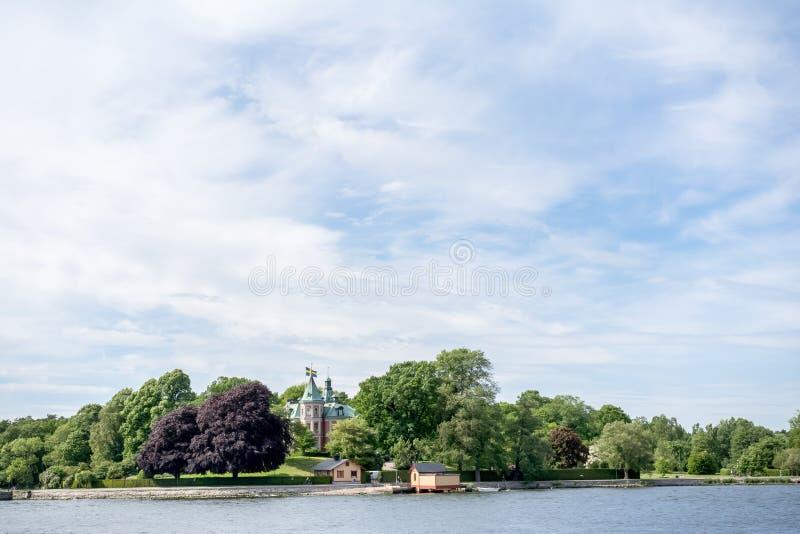 ΣΤΟΚΧΟΛΜΗ, ΣΟΥΗΔΙΑ - 6 ΙΟΥΝΊΟΥ 2016: Παράκτια άποψη ενός παλαιού μικρού κάστρου με τις σουηδικές σημαίες σε ένα νησί του αρχιπελά στοκ εικόνα με δικαίωμα ελεύθερης χρήσης
