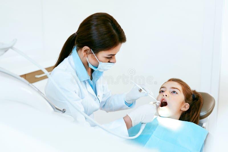 Στοματολογία Οδοντίατρος που εργάζεται με τα δόντια κοριτσιών στην οδοντική κλινική στοκ εικόνα