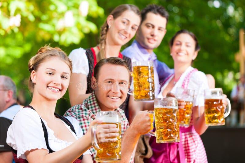 Στον κήπο μπύρας - φίλοι που πίνουν την μπύρα στοκ εικόνες