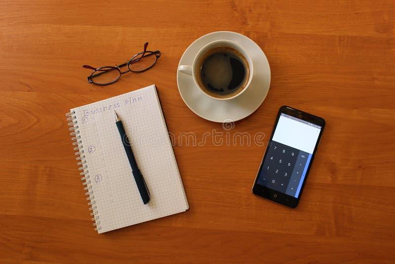 Στον πίνακα ένα φλυτζάνι του σημειωματάριου στιγμιαίου καφέ και του τηλεφώνου γυαλιών στοκ φωτογραφίες