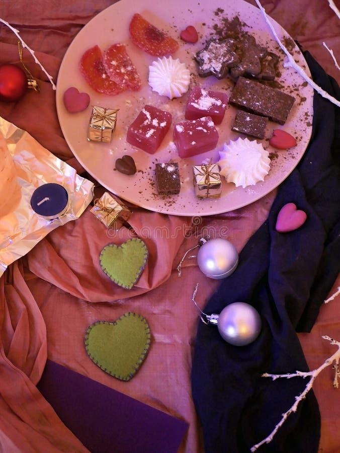 Στον πίνακα πιάτα στα ρόδινα υφασμάτων με ποικίλα γλυκά, ρομαντικό και ντεκόρ Χριστουγέννων, καρδιές, φρούτα, εποχιακό χειμερινό  στοκ φωτογραφία
