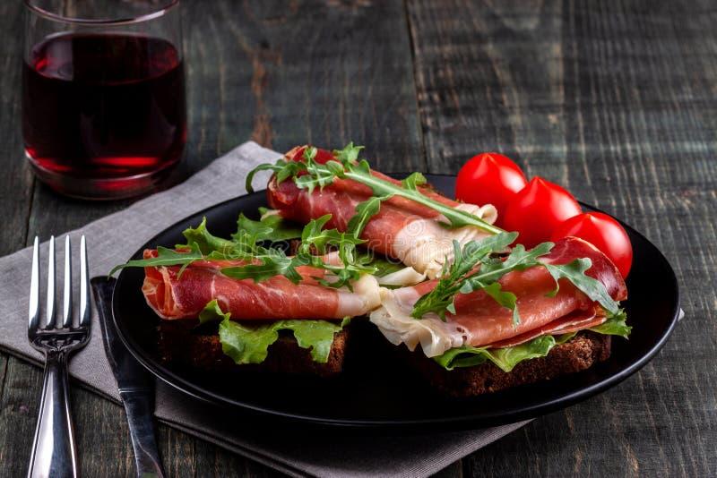 Στον πίνακα υπάρχει ένα πιάτο με τα σάντουιτς jamon, την ντομάτα, τα πράσινα και ένα ποτήρι του κόκκινου κρασιού στοκ εικόνες