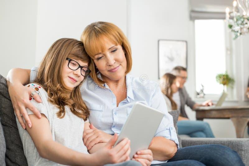 Στοργικές μητέρα και κόρη που χρησιμοποιούν την ψηφιακή ταμπλέτα με την οικογενειακή συνεδρίαση στο υπόβαθρο στο σπίτι στοκ φωτογραφία