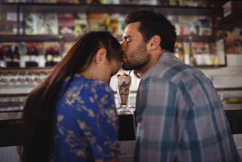 Στοργική φιλώντας γυναίκα ανδρών στο μετρητή στοκ εικόνα