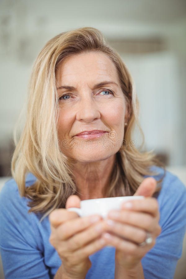 Στοχαστική ανώτερη γυναίκα που έχει το φλιτζάνι του καφέ στο καθιστικό στοκ εικόνα