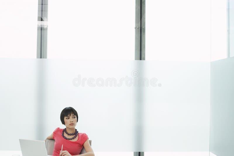 Στοχαστική γυναίκα με το lap-top στο σύγχρονο θαλαμίσκο στοκ εικόνες