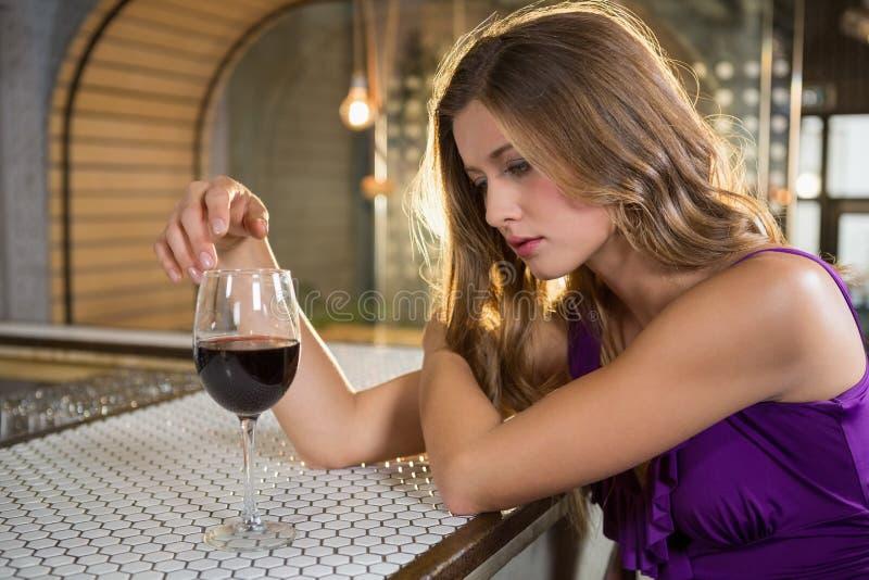 Στοχαστική γυναίκα που έχει το κόκκινο κρασί στο μετρητή φραγμών στοκ φωτογραφία με δικαίωμα ελεύθερης χρήσης