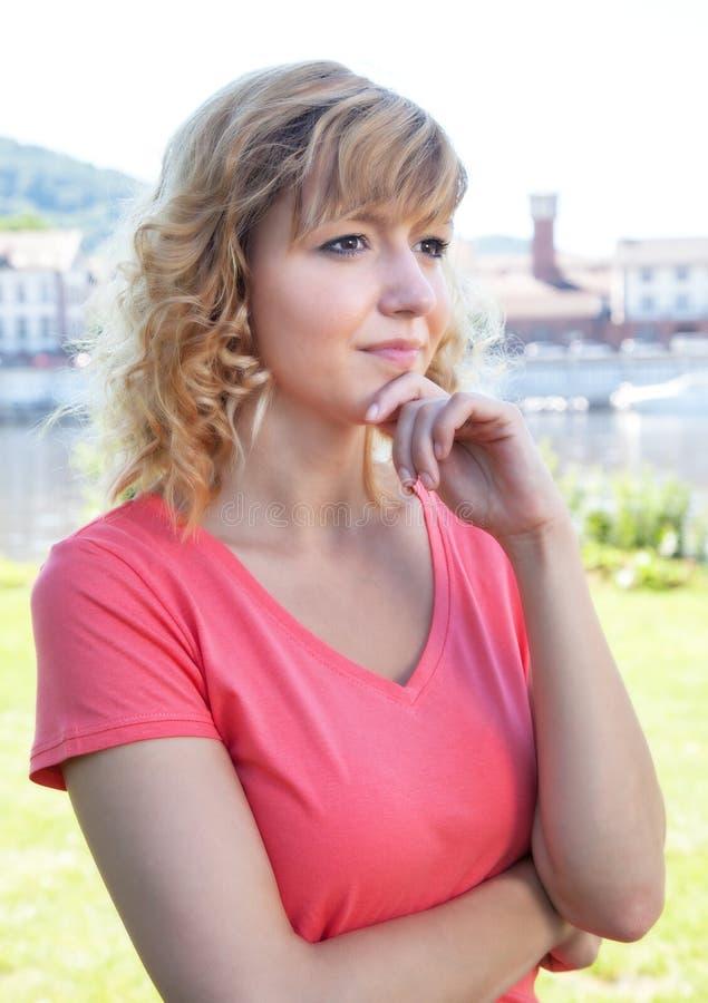 Στοχαστική γυναίκα σε ένα ρόδινο πουκάμισο έξω στοκ φωτογραφίες με δικαίωμα ελεύθερης χρήσης