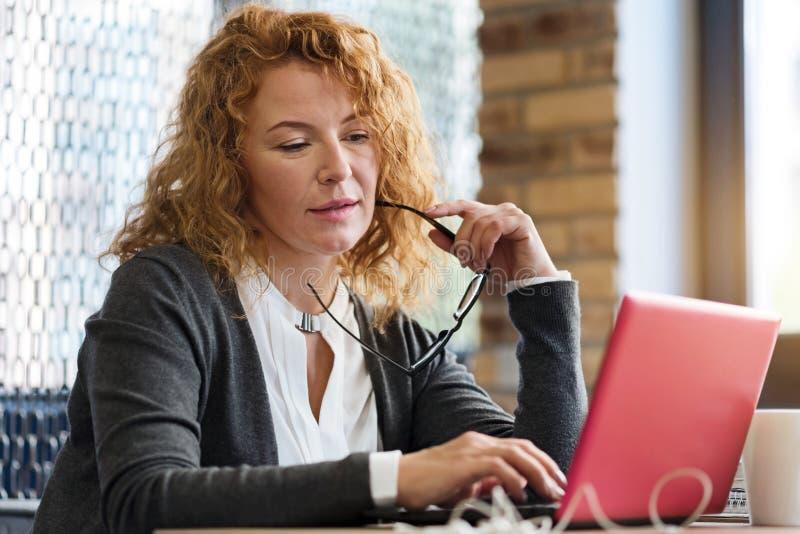 Στοχαστική γυναίκα στον καφέ με το lap-top στοκ εικόνες