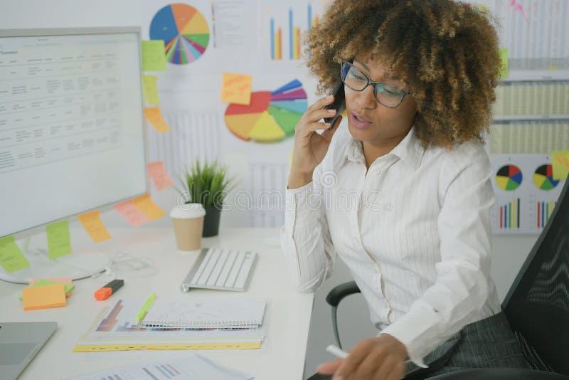 Στοχαστική γυναίκα στο γραφείο που μιλά στο τηλέφωνο στοκ εικόνες