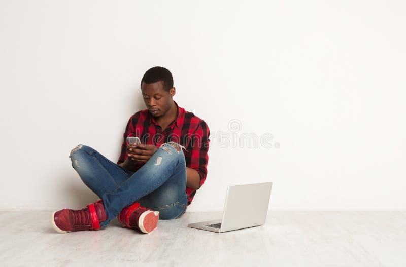 Στοχαστική δακτυλογράφηση μαύρων στο smartphone, συνεδρίαση lap-top στο πάτωμα στούντιο στοκ φωτογραφία με δικαίωμα ελεύθερης χρήσης