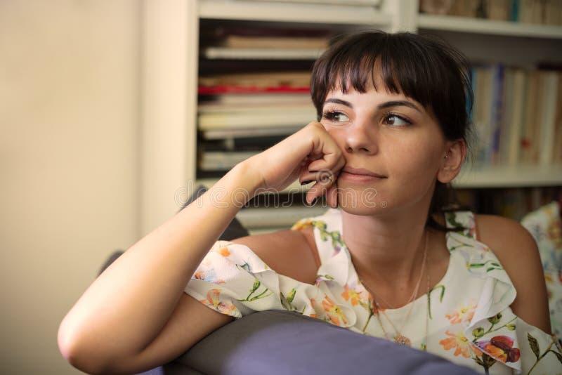 Στοχαστική ελκυστική νέα συνεδρίαση γυναικών στο εσωτερικό στοκ φωτογραφία με δικαίωμα ελεύθερης χρήσης
