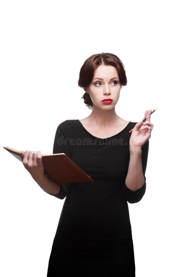 Στοχαστική επιχειρησιακή γυναίκα με το ημερολόγιο στοκ εικόνα