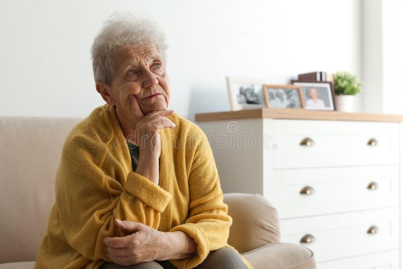 Στοχαστική ηλικιωμένη γυναίκα στον καναπέ στοκ φωτογραφία με δικαίωμα ελεύθερης χρήσης
