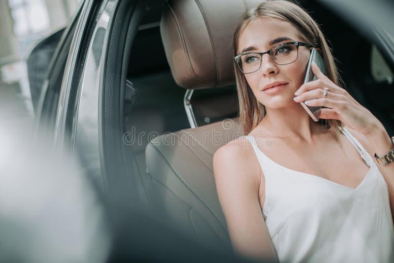 Στοχαστική θηλυκή ομιλία σε κινητό στο αυτοκίνητο στοκ εικόνα