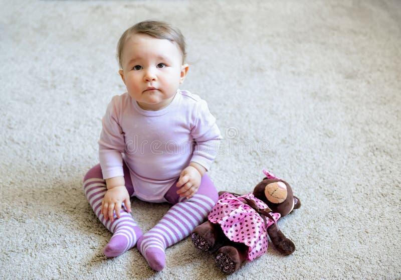 Στοχαστική και σοβαρή συμπαθητική συνεδρίαση κοριτσάκι στο πάτωμα στοκ εικόνα με δικαίωμα ελεύθερης χρήσης
