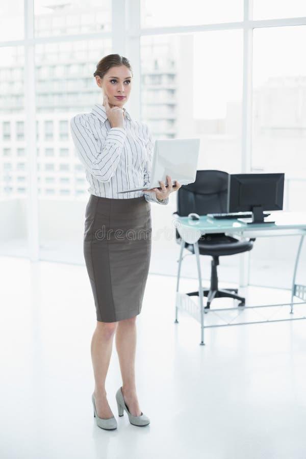 Στοχαστική κομψή επιχειρηματίας που κρατά το σημειωματάριό της στοκ εικόνες