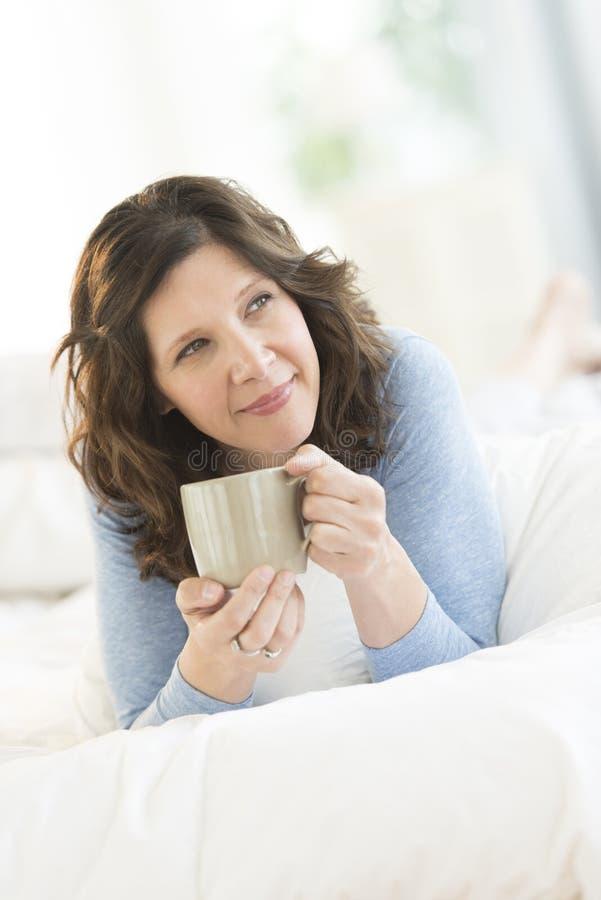 Στοχαστική κούπα καφέ εκμετάλλευσης γυναικών στο κρεβάτι στοκ εικόνες