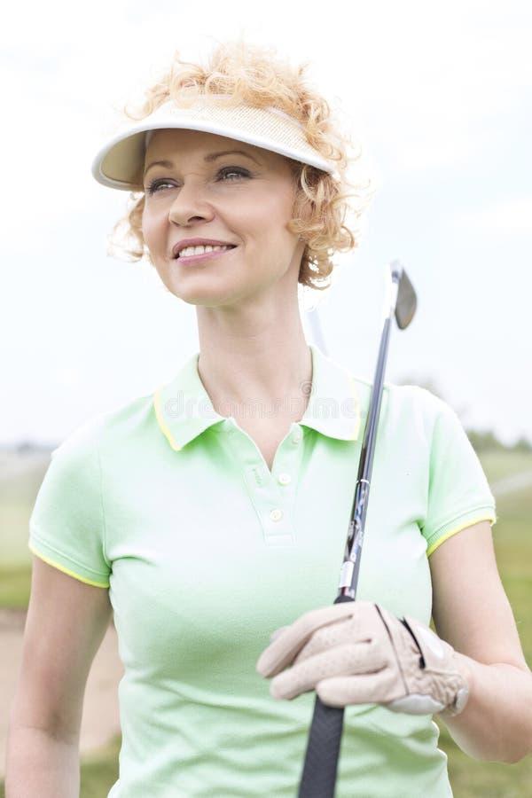 Στοχαστική μέσης ηλικίας γυναίκα που κοιτάζει μακριά κρατώντας το γκολφ κλαμπ στοκ εικόνα