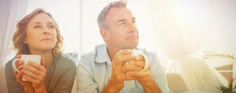 Στοχαστική μέση ηλικίας συνεδρίαση ζευγών στον καναπέ που έχει τον καφέ στοκ φωτογραφία με δικαίωμα ελεύθερης χρήσης