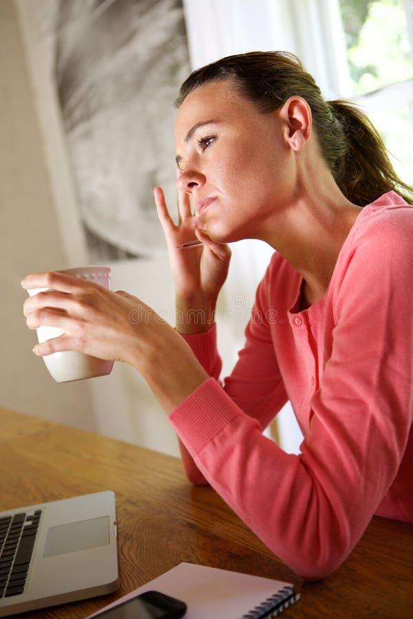 Στοχαστική νέα γυναίκα με τον καφέ στο σπίτι στοκ φωτογραφία με δικαίωμα ελεύθερης χρήσης