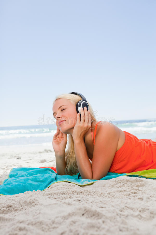 Στοχαστική νέα γυναίκα που βρίσκεται στην παραλία στοκ φωτογραφίες