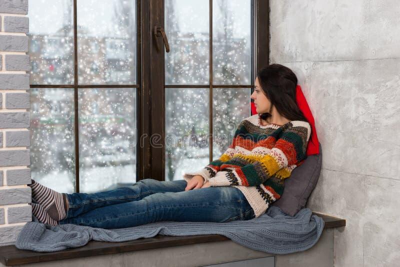Στοχαστική νέα γυναίκα που ξαπλώνει στα μαξιλάρια στο windowsi στοκ εικόνα