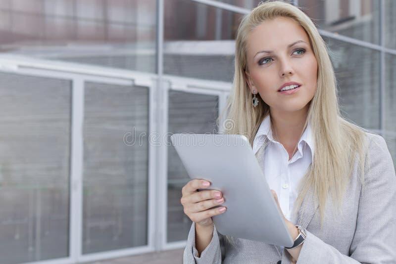 Στοχαστική νέα επιχειρηματίας που χρησιμοποιεί την ψηφιακή ταμπλέτα κοιτάζοντας μακριά ενάντια στο κτίριο γραφείων στοκ εικόνα
