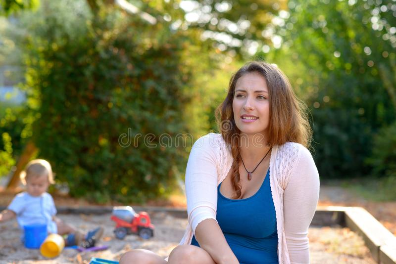 Στοχαστική νέα μητέρα που παίζει υπαίθρια στοκ εικόνες με δικαίωμα ελεύθερης χρήσης