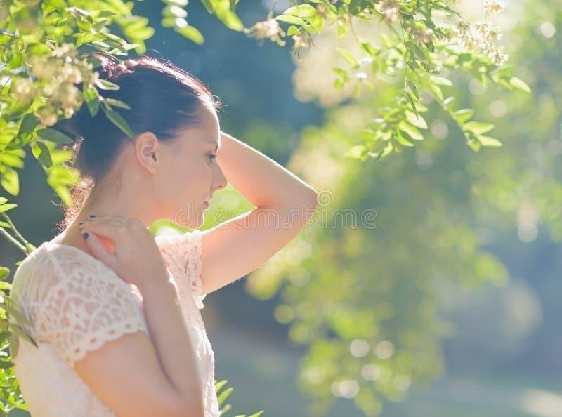Στοχαστική νέα χαλάρωση γυναικών στο δάσος στοκ φωτογραφίες