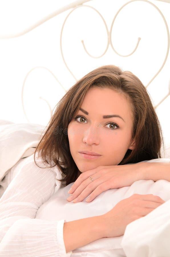 Στοχαστική νέα όμορφη γυναίκα στο κρεβάτι στοκ φωτογραφία