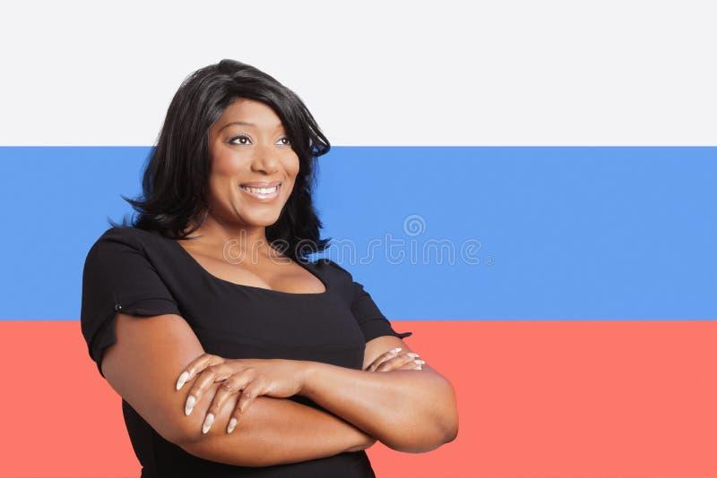 Στοχαστική περιστασιακή μικτή γυναίκα φυλών πέρα από τη ρωσική σημαία στοκ εικόνα με δικαίωμα ελεύθερης χρήσης
