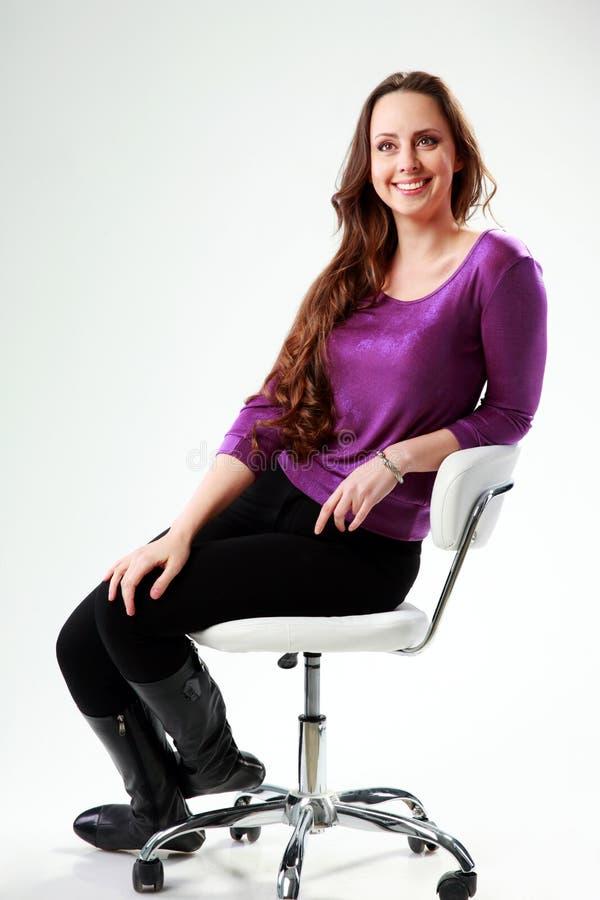Στοχαστική συνεδρίαση γυναικών χαμόγελου στην καρέκλα στοκ εικόνες με δικαίωμα ελεύθερης χρήσης