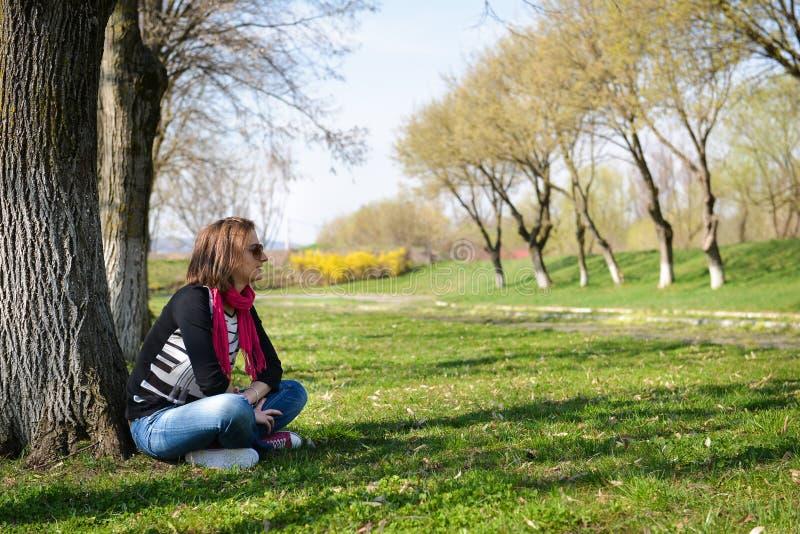Στοχαστική συνεδρίαση brunette κάτω από ένα δέντρο στο πάρκο σε μια ηλιόλουστη DA στοκ φωτογραφία