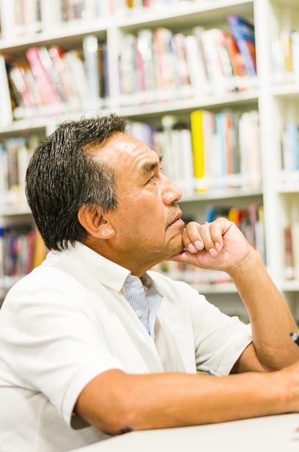 Στοχαστικός ανώτερος άνδρας σπουδαστής με το χέρι στο πηγούνι που κοιτάζει μακριά στη βιβλιοθήκη στοκ φωτογραφία με δικαίωμα ελεύθερης χρήσης