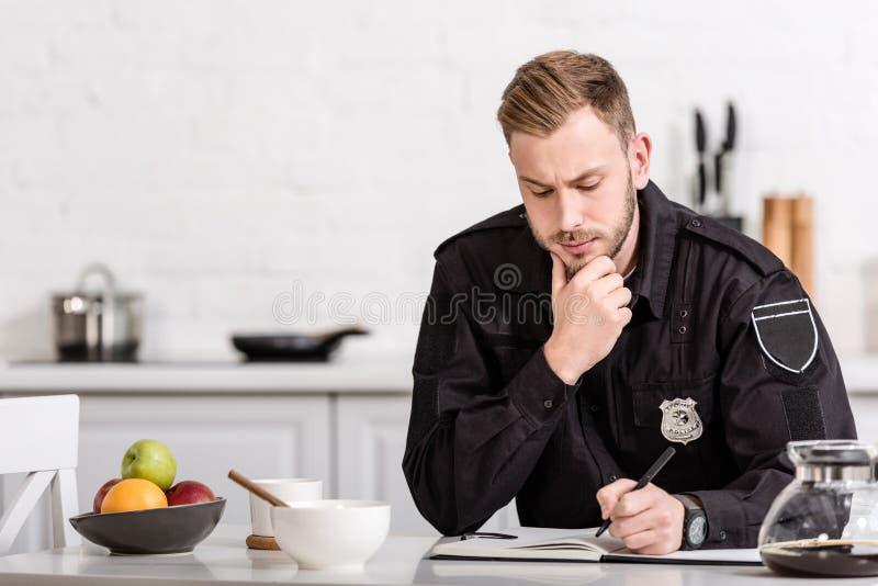 στοχαστικός αστυνομικός που γράφει στο σημειωματάριο στοκ φωτογραφία