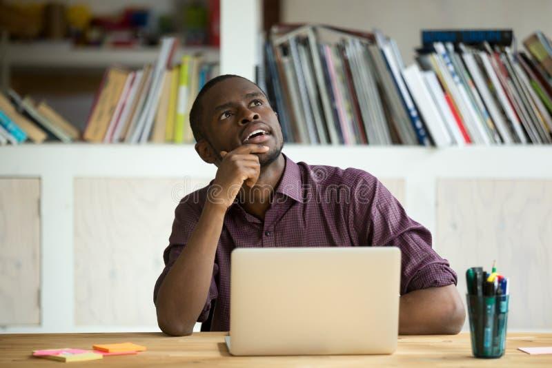 Στοχαστικός μαύρος εργαζόμενος που ονειρεύεται για τα μελλοντικά επιτεύγματα στοκ εικόνες
