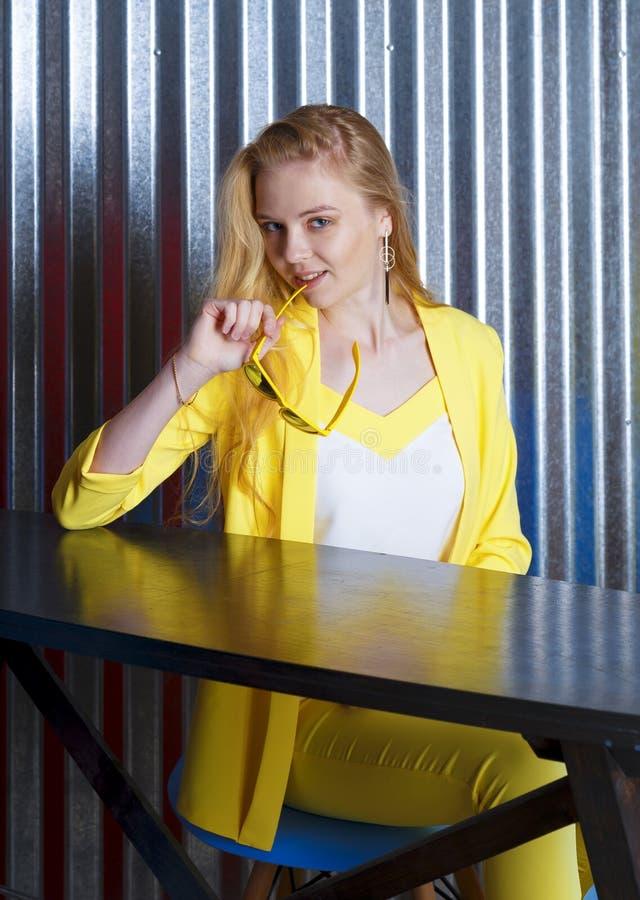 Στοχαστικός νέος ξανθός δεσμός δαγκωμάτων γυναικών των γυαλιών που κάθονται στον πίνακα στοκ εικόνες