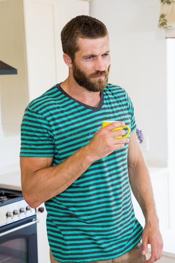Στοχαστικό άτομο που έχει έναν καφέ στην κουζίνα στοκ φωτογραφία με δικαίωμα ελεύθερης χρήσης