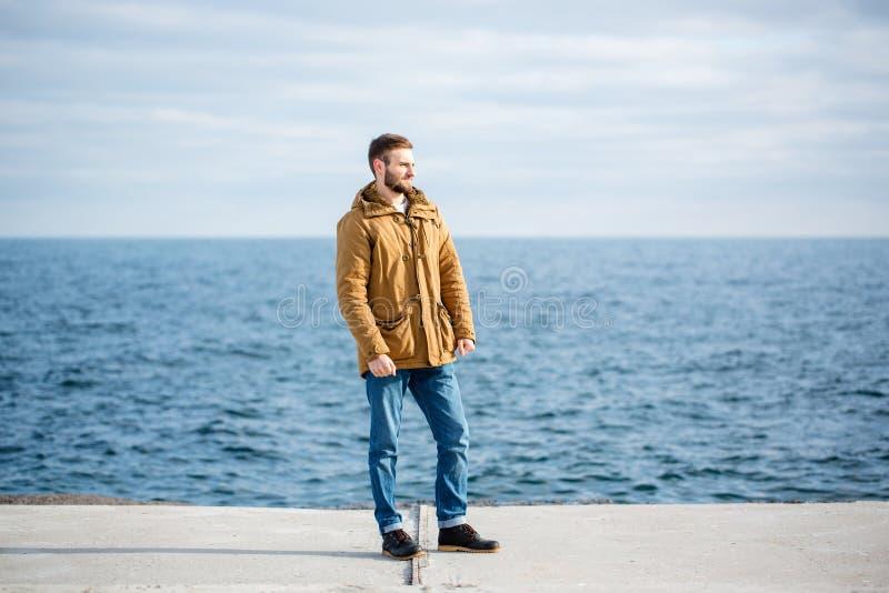 Στοχαστικό άτομο που στέκεται στην αποβάθρα κοντά στη θάλασσα στοκ φωτογραφίες