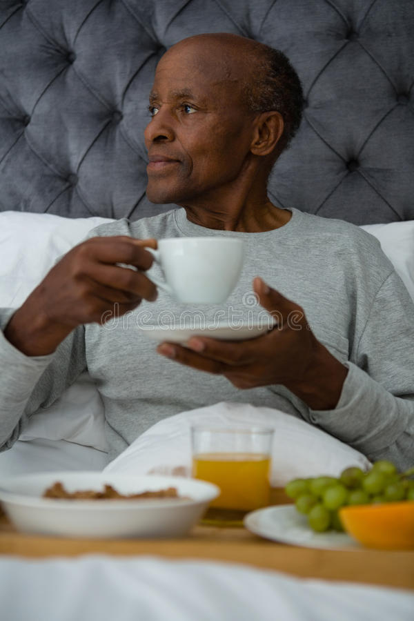 Στοχαστικό ανώτερο άτομο που κοιτάζει μακριά ενώ έχοντας το πρόγευμα στο κρεβάτι στοκ φωτογραφία με δικαίωμα ελεύθερης χρήσης