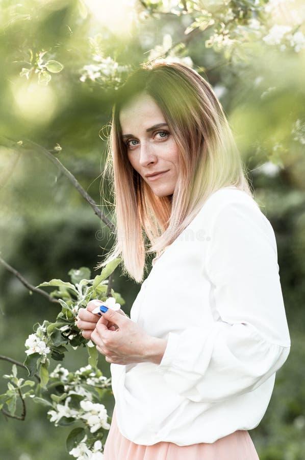 Στοχαστικό κορίτσι άνοιξη στον ανθίζοντας οπωρώνα μήλων στοκ εικόνες