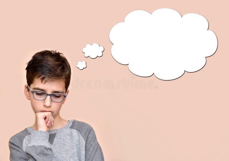 Στοχαστικό νέο αγόρι με μια κενή σκεπτόμενη φυσαλίδα στοκ εικόνα με δικαίωμα ελεύθερης χρήσης